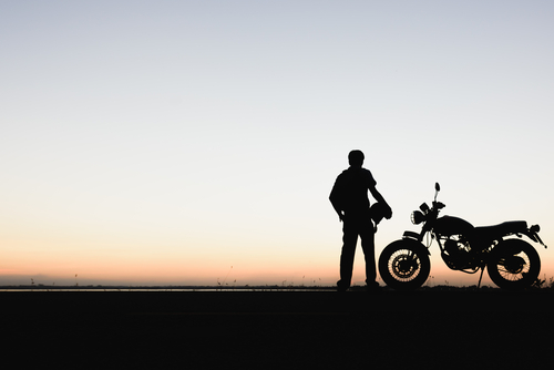 Someone with a motorcycle, watching the sun set